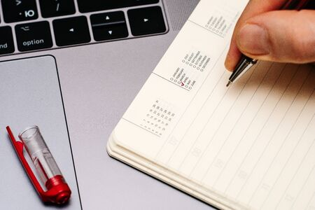 male hand encircles date month April in the diary calendar. on a laptop with a red pen