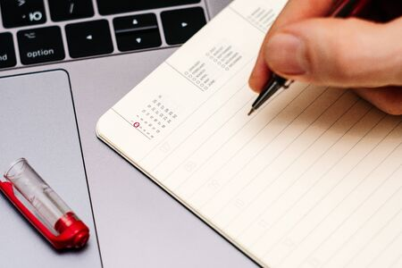 male hand encircles date 2 (two) in the diary calendar. on a laptop with a red pen