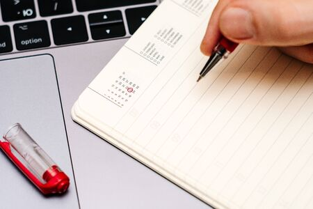 male hand encircles date 23 (twenty three) in the diary calendar. on a laptop with a red pen