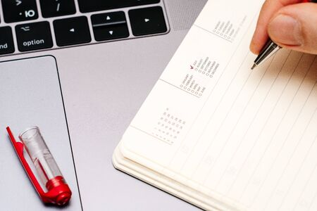 male hand encircles date month July in the diary calendar. on a laptop with a red pen