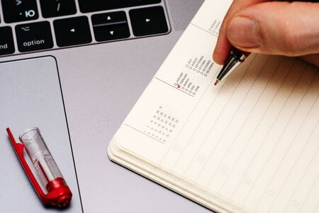 male hand encircles date month February in the diary calendar. on a laptop with a red pen