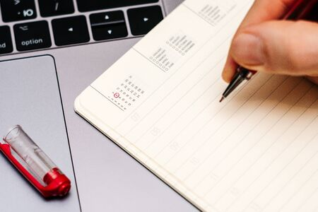 male hand encircles date 8 (eight) in the diary calendar. on a laptop with a red pen