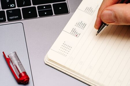 male hand encircles date month May in the diary calendar. on a laptop with a red pen