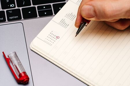 male hand encircles date 30 (thirty) in the diary calendar. on a laptop with a red pen