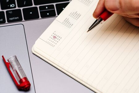 male hand encircles date 21 (twenty one) in the diary calendar. on a laptop with a red pen 스톡 콘텐츠