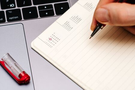male hand encircles date 14 (fourteen) in the diary calendar. on a laptop with a red pen