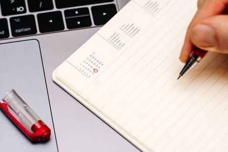 male hand encircles date 18 (eighteen) in the diary calendar. on a laptop with a red pen 스톡 콘텐츠