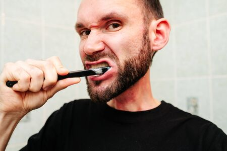 Portrait of handsome man getting hurt while shaving with a razor