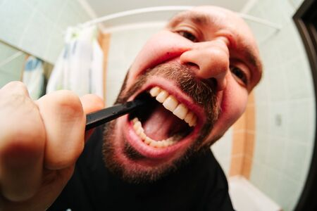 Portrait of handsome naked man getting hurt while shaving with a razor