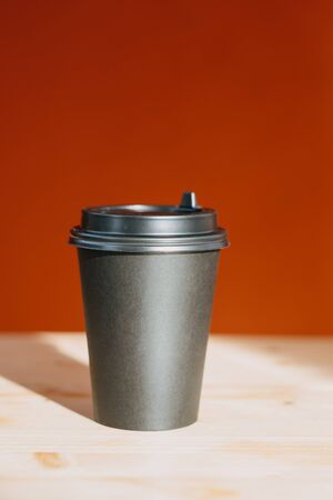 coffee to go. black glass for coffee on a table on a red background backlit by the sun. Close-up