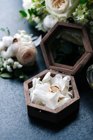 bridal bouquet, boutonniere, rings in a casket, perfume.