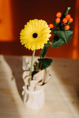 yellow gerbera flower in a craft vase on a table backlit by the sun Фото со стока