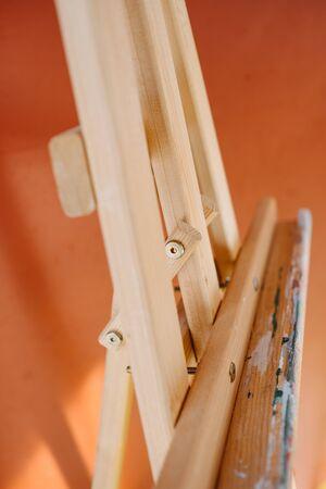 wooden easel on an orange background.