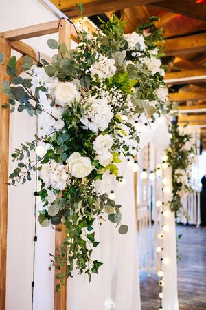 Wedding arch made of fabric and white and pink flowers in a wooden room