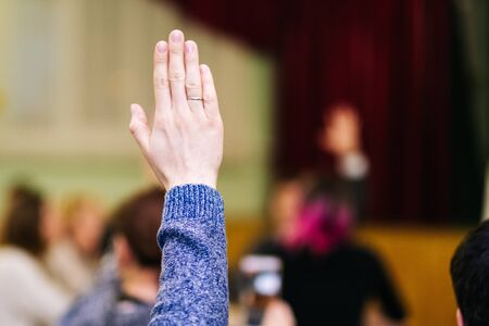 a man raises his right hand in a meeting. Voting
