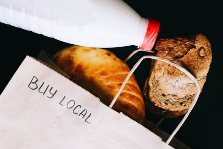 Buy local. milk and bread on a black table with a craft bag