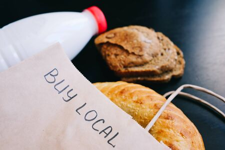 Buy local. milk and bread on a black table with a craft bag. view from above