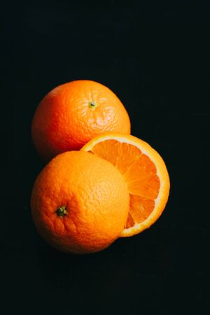 Vertical poster photo of an orange on a black background with light coming from top Фото со стока
