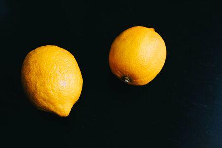 fresh lemon on black background. two lemons. Horizontal frame close up