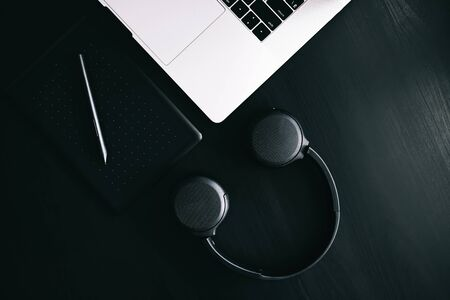 Dark modern workplace with a graphic tablet, laptop, wireless headphones
