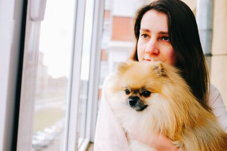 Smiling woman hugging a cute fluffy pomeranian spitz dog looking out the window