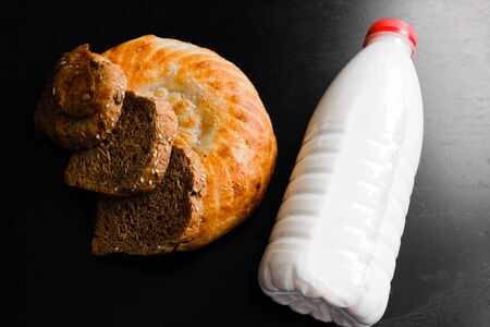 milk and bread on a black table. view from above