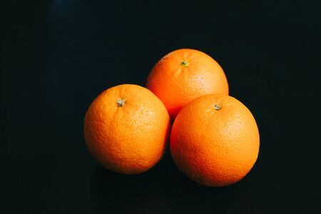 Vertical poster photo of an orange on a black background with light coming from top Фото со стока - 146113371