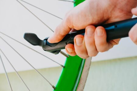 a man pumps up a green bicycle wheel with a hand pump