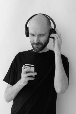 A bald man with wireless headphones and smartphone Фото со стока