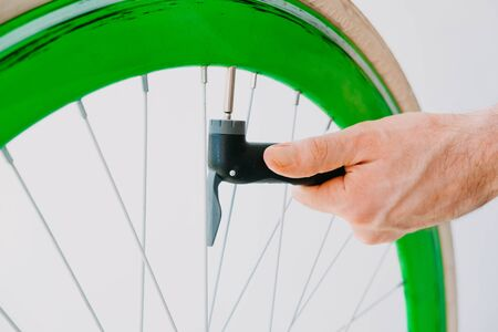 a man pumps up a green bicycle wheel with a hand pump. close-up