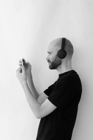 man with wireless headphones and a smartphone in his hands takes pictures