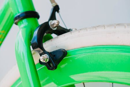 brakes of a green fix bike with white tires. Close-up