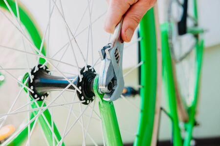 a man spins a wheel of a green bicycle with white wheels