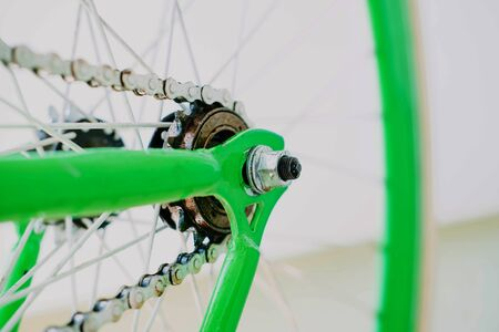 rear wheel closeup of green fix bike with white chain. close-up