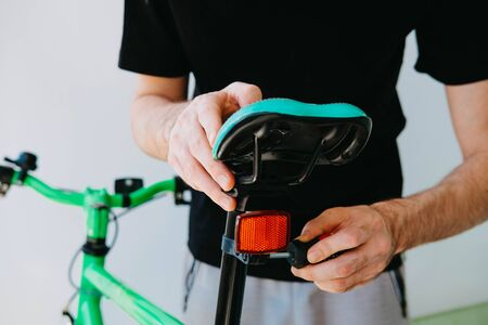 Installation of a rear reflective green fix bike with white tires. Close-up
