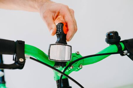 Installation of a front reflective green fix bike with white tires. Close-up Фото со стока