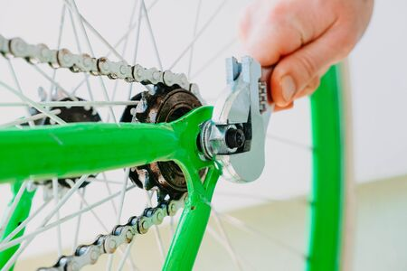 a man spins a wheel of a green bicycle with white wheels. close-up