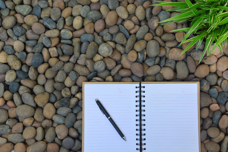 note booklet: blank notebook and a pen on the stone background