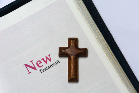 new testament: New testament cover in Holy Bible with a wooden cross