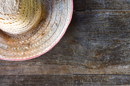 wicker work: half striped farmer hat made of woven bamboo on old wood background, copy space Stock Photo