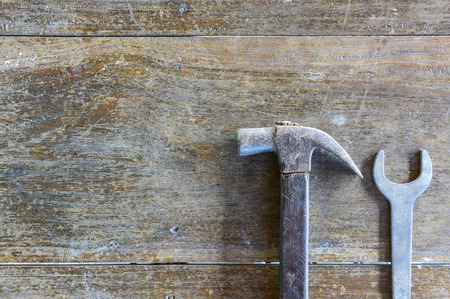 pounding head: hammers and  wrench on old wood background, copy space Stock Photo