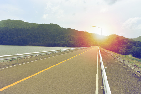 field stripped: empty road on dam with sunrise above Stock Photo