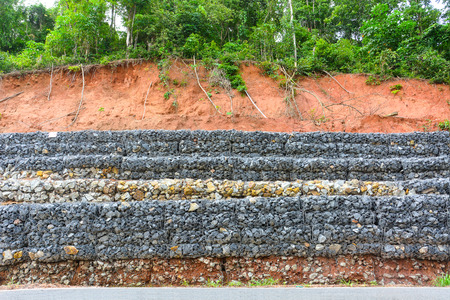 gabion mesh: Gabion wall made of stones in the steel mesh, used as a fence on a slope for protection landslide