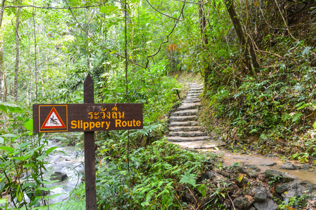 slippery route sign along the way to waterfall in tropical fores