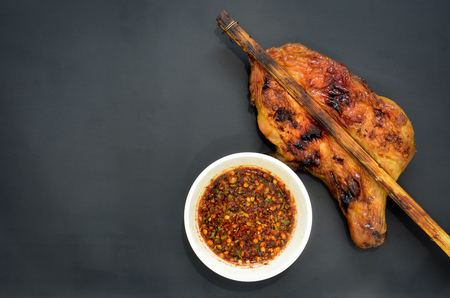 quemado: grilled chicken with Thai style dipping spicy sauce for roasted or grilled food (fish sauce and chilli) or Nam Jim Jaew, Thai street food, on black background, copy space