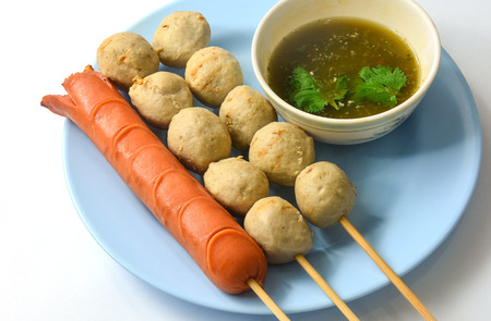 Thai street food, grilled hotdog and meatball with spicy seafood sauce on white background
