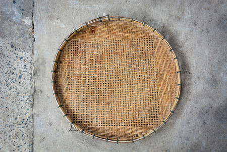 winnowing basket, bamboo threshing basket use for food airing on cement floor background Stock Photo