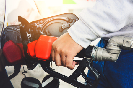 man holding red fueling nozzle and pumping gasoline fuel fill in car at gas station, vintage effect, car fuels or transportation concept