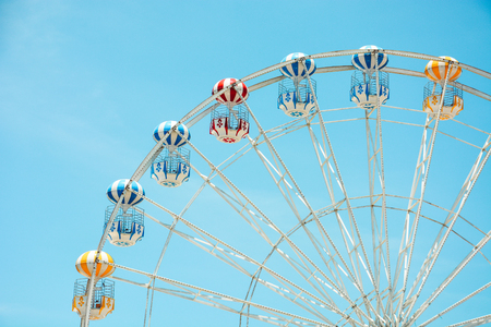 front view of half retro colorful ferris wheel at amusement park over blue sky background, copy space, vintage effect