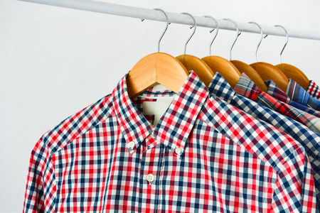 close up clothes hang on shelf or clothing rack, long sleeve red and blue checkered shirt on wooden hanger over white background, copy space Stock Photo